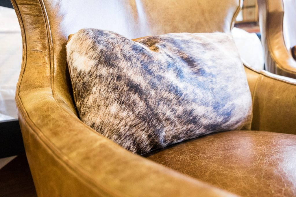 animal print patterned pillow on a light brown leather couch