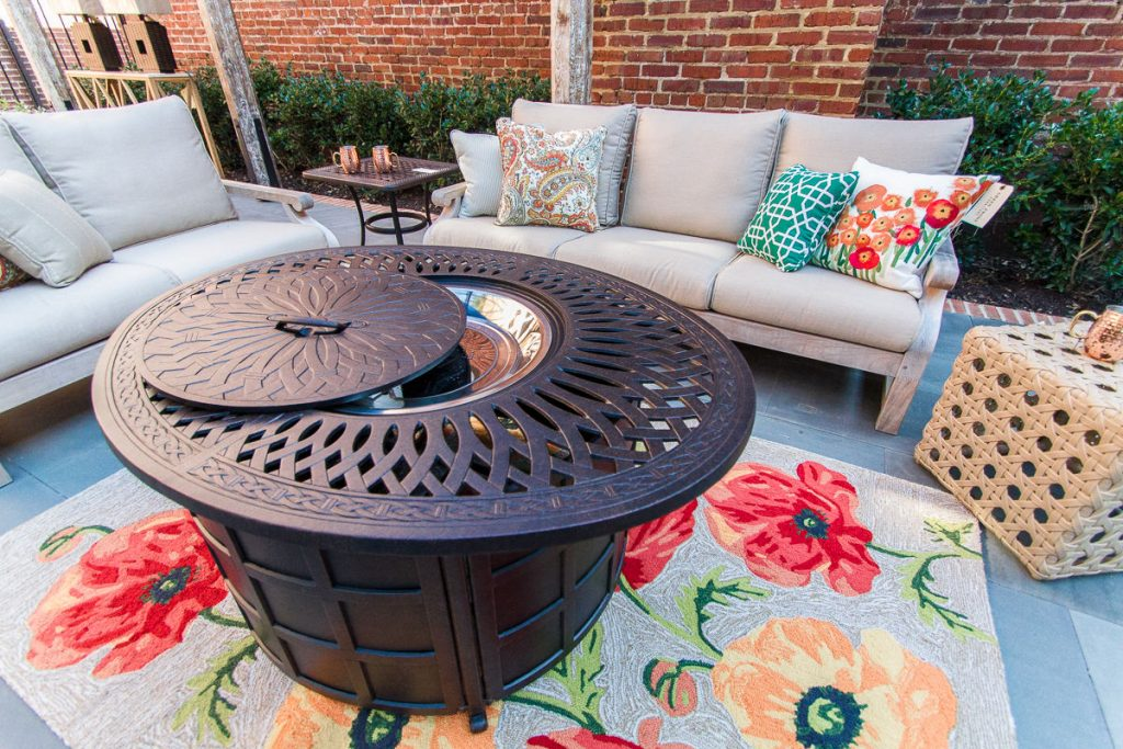 brown metal fire pit on a floral rug in front of two beige couches